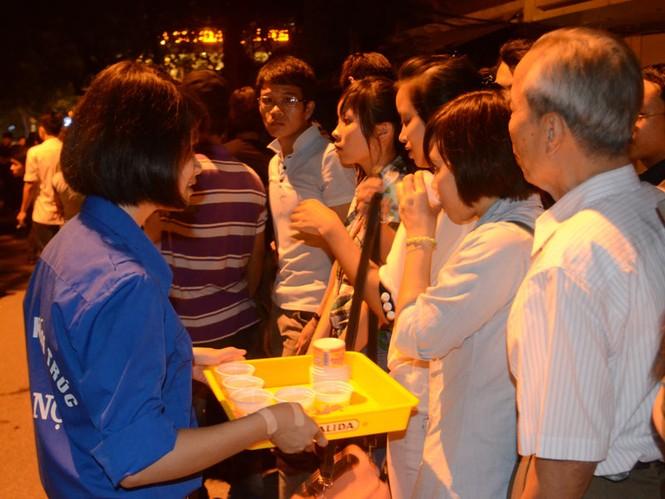 Tình nguyện viên mời người dân uống nước trong khi xếp hàng chờ viếng. Ảnh: Tiền Phong