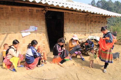 Gần trưa, khi ánh mặt trời ló qua các đỉnh núi mây mù, phụ nữ Mông gọi nhau địu con ra hiên nhà ngồi sửa ấm, tranh thủ thêu thùa váy áo mới chuẩn bị đi chơi Tết