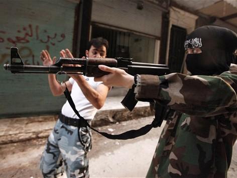 """Một tay súng nữ thuộc tiểu đoàn """"Mẹ Aisha"""" đang được hướng dẫn bắn súng trong khóa huấn luyện quân sự ở tỉnh Aleppo của Syria. Ảnh: Telegraph"""