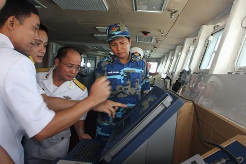 Hoa tiêu Trung Quốc (thứ hai từ trái) đang cung cấp thông tin về cảng Trạm Giang cho thuyền trưởng Nguyễn Đình Giảng và tổ lái tàu HQ-011