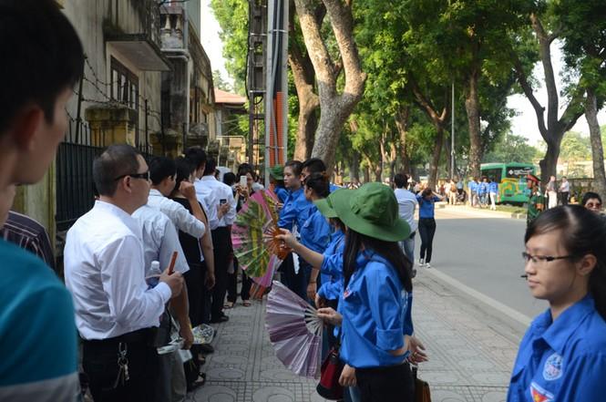 Những sinh viên tình nguyện quạt cho người dân đang xếp hàng