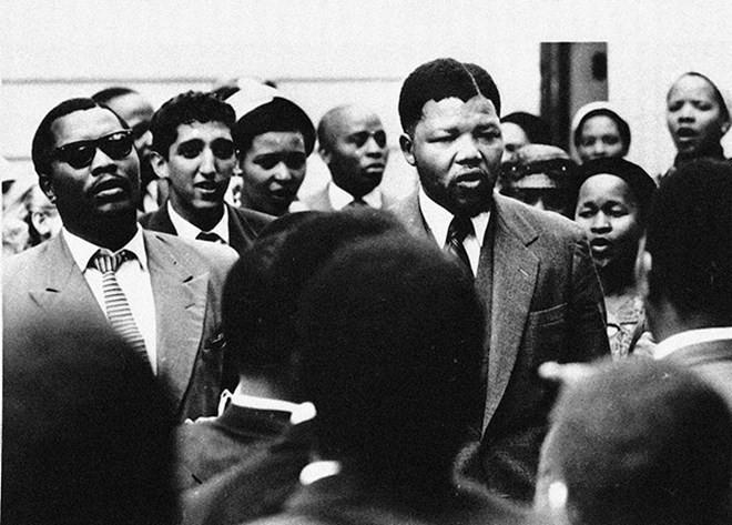 Năm 1956: Mandela hát với những người ủng hộ mình trong một phiên tòa xét xử ông phạm tội phản quốc. Sau quá trình xét xử kéo dài từ năm 1956-1961, ông và 150 người bị xử tội phản quốc trước đó được tuyên trắng án. (Nguồn: AP)