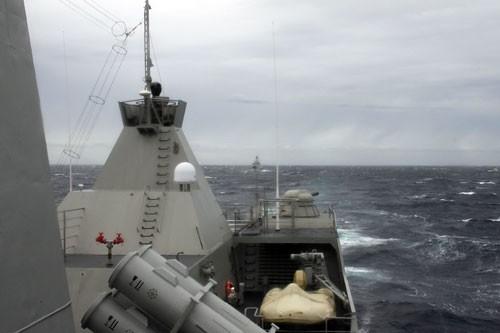 Hai chiến hạm Việt Nam tuần tra trên biển Đông dưới bầu trời xám xịt, gió giật từng cơn kinh hoàng