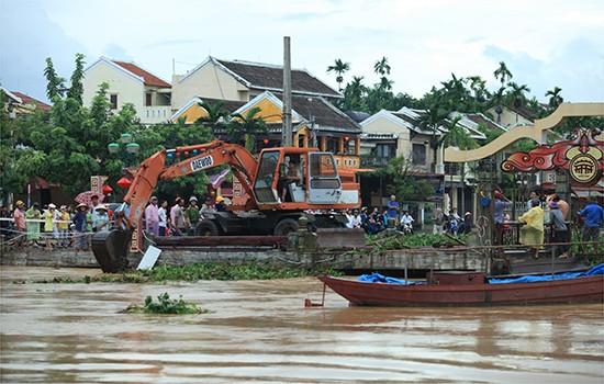 Dù đã được mở nắp khai thông ở điểm giữa cầu nhưng do bèo, rác dồn đọng sâu cả mét nên nước vẫn không thể chảy khiền tràn lên các tuyến phố
