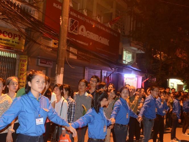 Các bạn sinh viên tình nguyện nắm tay nhau giúp đoàn người dài đi vào viếng Đại tướng