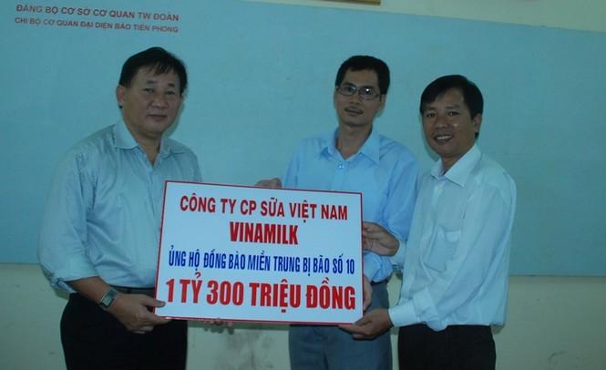 Ông Nguyễn Thanh Tú (trái) đại diện Công ty Vinamilk trao số tiền 1,3 tỷ đồng cho báo Tiền Phong