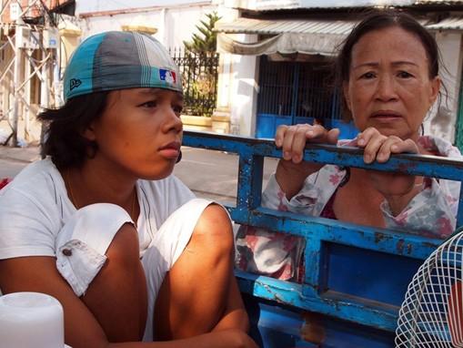Thái Kim Tài cùng mẹ bên thùng chiếc xe lôi chở đồ chuyển nhà. Ảnh: Hoàng Điệp