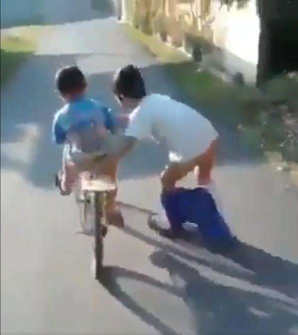 Video dễ thương nhất: Cậu bé giúp bạn tập đi xe đạp, không để bạn ngã dù mình… tuột cả quần - ảnh 1