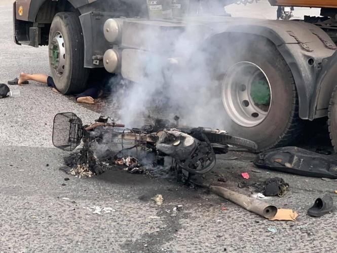 Xe máy cháy rụi sau khi bị container kéo lê trên đường - ảnh 1