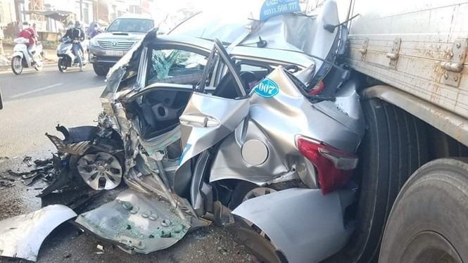 Taxi nát bét sau khi bị cuốn vào gầm xe tải - ảnh 1