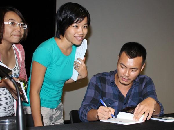 Nguyễn Thế Hoàng Linh ký tặng thơ độc giả tối 20-9. Ảnh: Cúc Chi