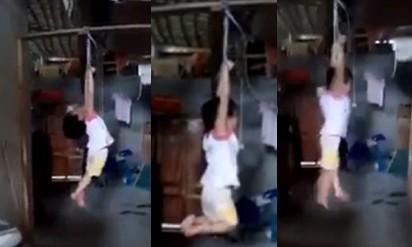 Hình ảnh bé gái bị treo lên xà nhà khiến dư luận phẫn nộ. Ảnh cắt từ clip