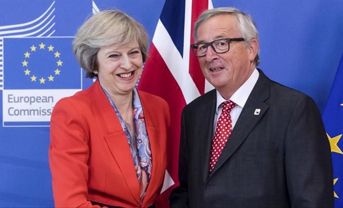 Thủ tướng Anh Theresa May và Chủ tịch Ủy ban châu Âu Jean-Claude Juncker vui mừng trong cuộc họp báo thông báo đạt được bước đột phá. Ảnh: Politicshome.