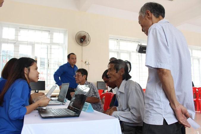 Các TNV hỗ trợ người dân đăng ký tài khoản công dân điện tử và hướng dẫn thực hiện các dịch vụ công trực tuyến trên máy tính. Ảnh: Giang Thanh.