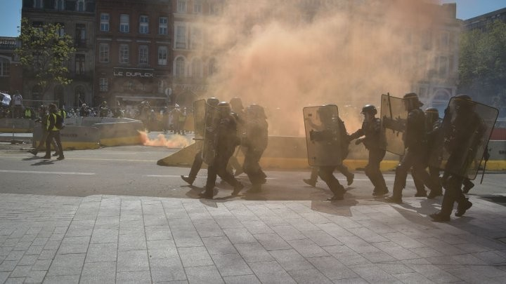 Cảnh sát chống biểu tình di chuyển giữa khói mù trong cuộc biểu tình lần thứ 22 liên tiếp vào ngày thứ bảy của phong trào 'Áo vàng'