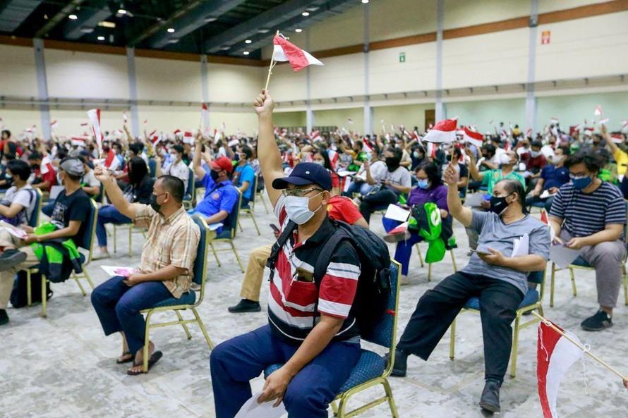 Người dân Indonesia cầm quốc kì khi đi tiêm vắc xin ở Jakarta. Ảnh: Reuters