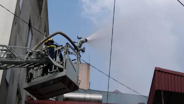 Lính cứu hỏa dùng xe thang chữa cháy.